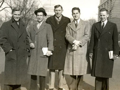 black and white photo of men in winter coats