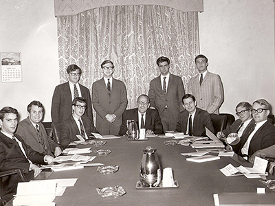 black and white photo of men in suits around a table