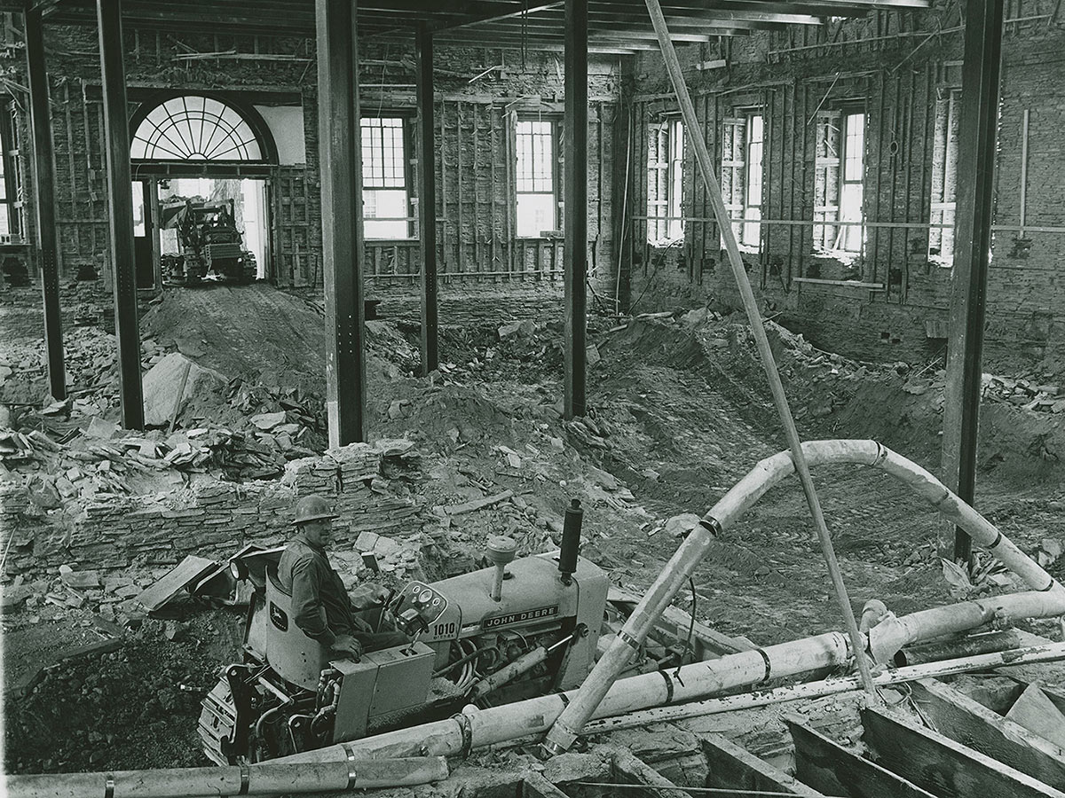 A construction worker drives a bulldozer inside the gutted interior of Alumni Hall