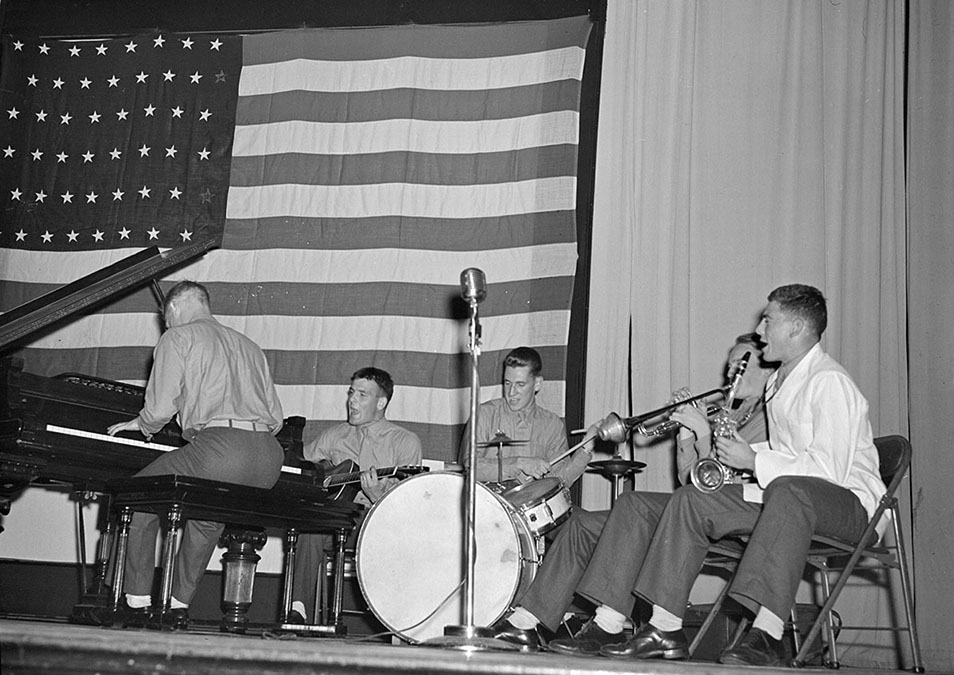 Members of a Marine cadet band perform on stage for student event, 1943