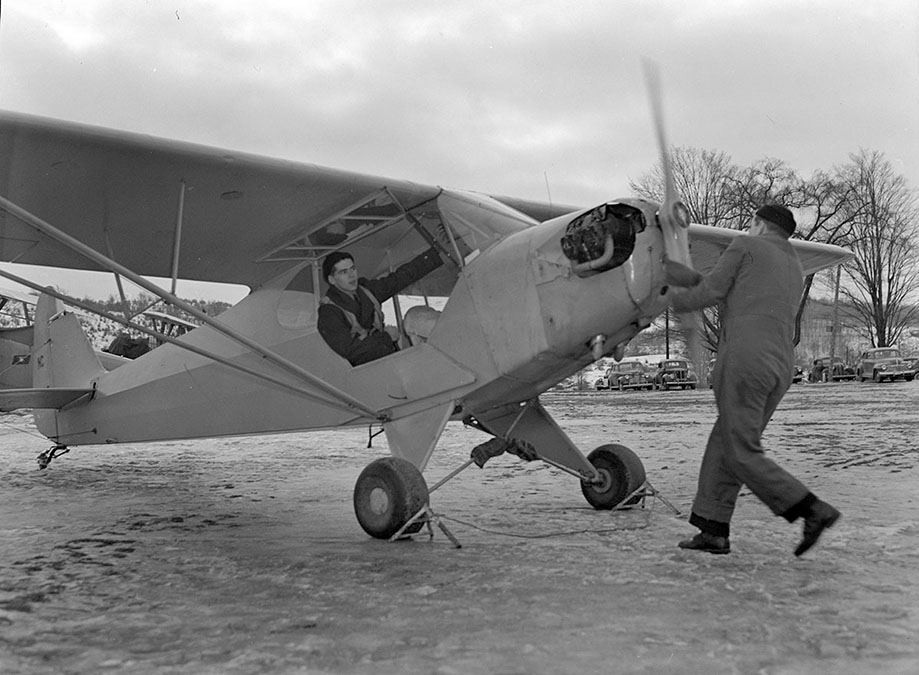 Navy Flight Preparatory School cadet starts airplane by turning propeller, 1944