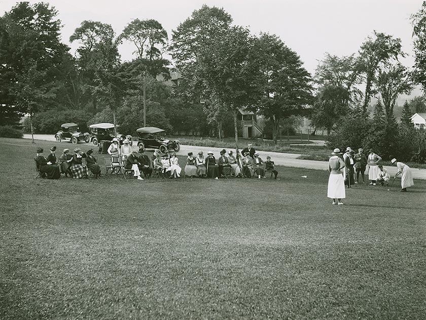 A woman in a long dress prepares to put in a group of golfers, observed by a group in lawn chairs