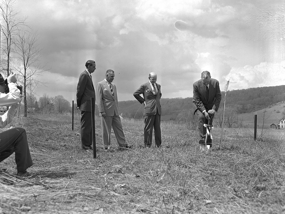 Three men observe as a fourth breaks ground with a shovel. A photographer snaps a photo from the left.