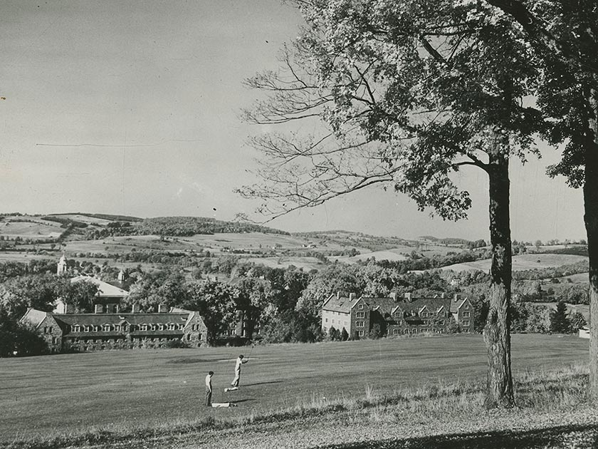 Two golfers on the old golf course, with Andrews and Stillman Halls visible in the background