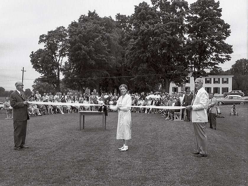 Two men hold a ribbon while a woman cuts it, and a crowd watches. The clubhouse is visible in the background