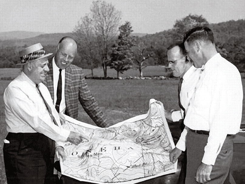 Four men look over a map while in a field