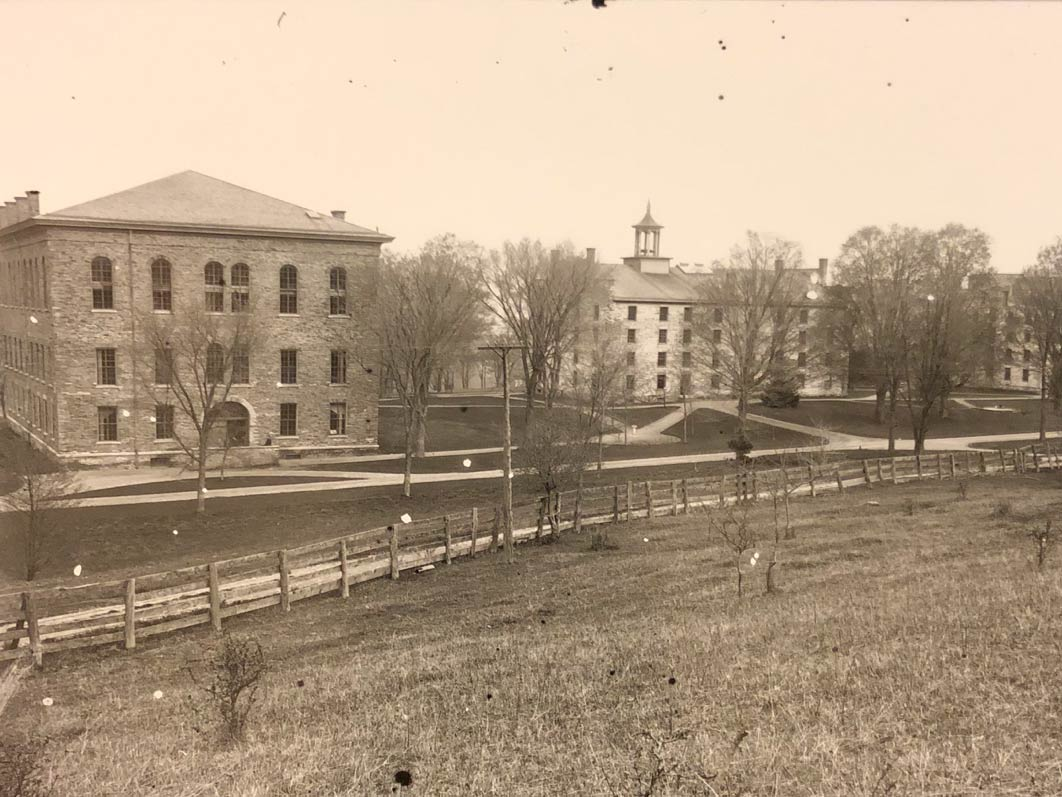 Archival image of Alumni Hall, the Western Edifice, and the Eastern Edifice, as seen from further up the hill