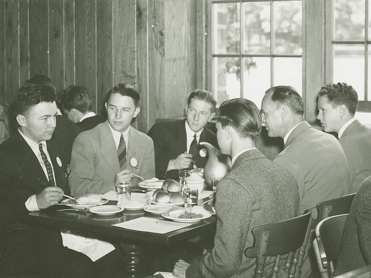 Students in jackets and ties eating dinner