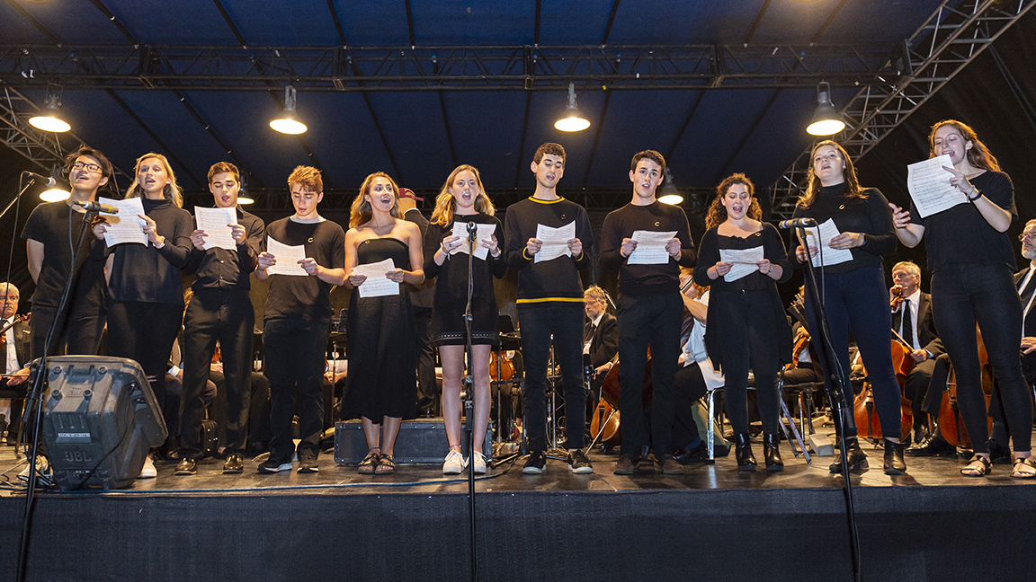 Students sing on stage with Symphoria