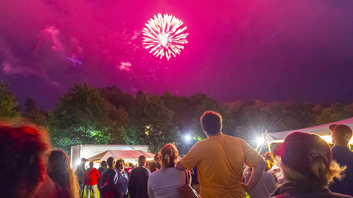Attendees watch fireworks blossoming over the hill