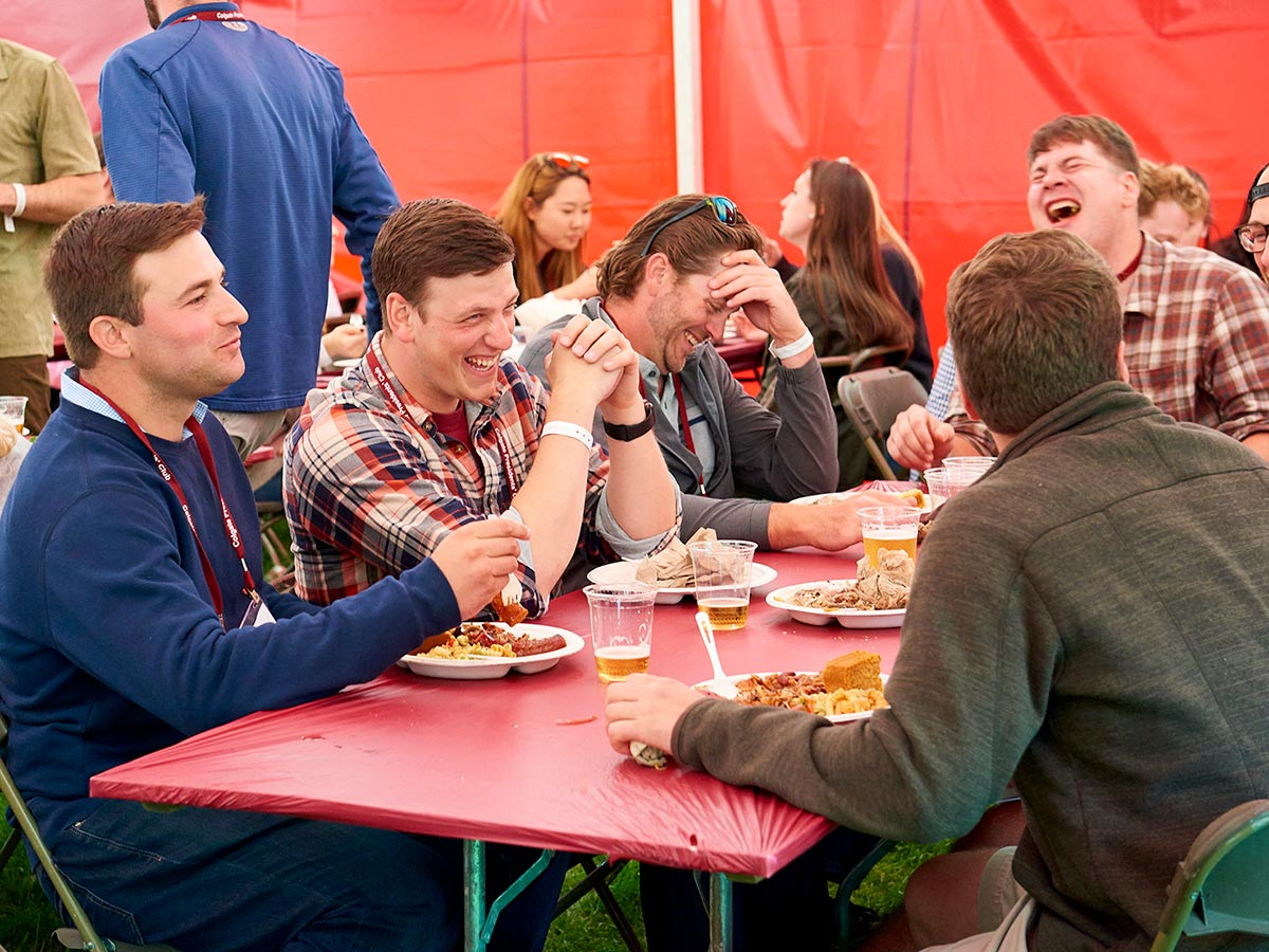 Alumni laugh while sharing a meal in a Reunion tent.