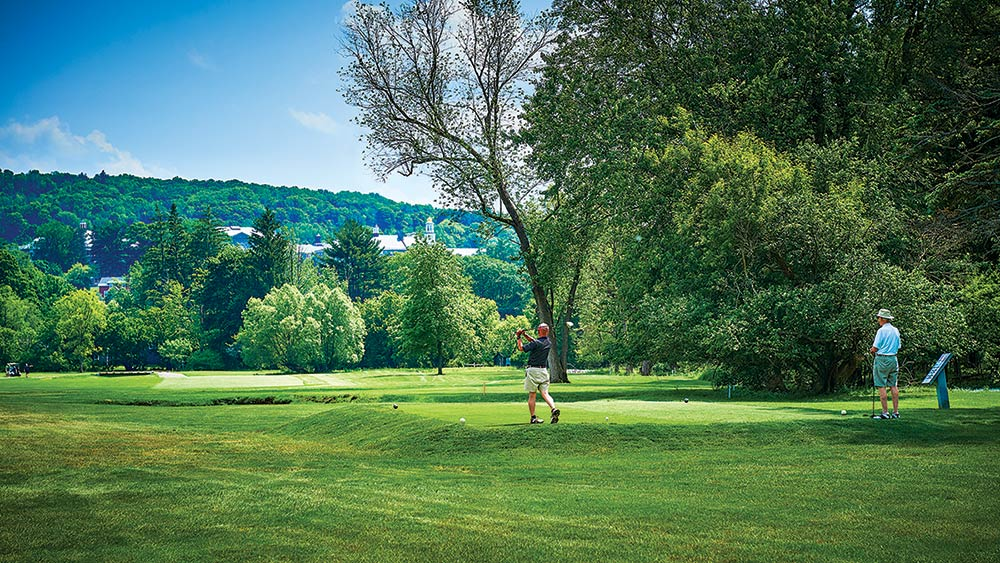 Golfer drives from the tee with the Colgate campus on a hillside in the background