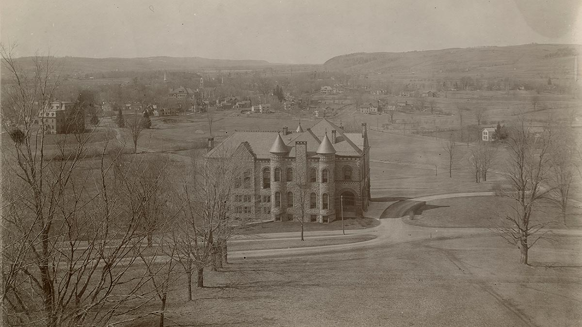 Black and white photo of James B. Colgate Hall and the valley below, seen from partway up the hill