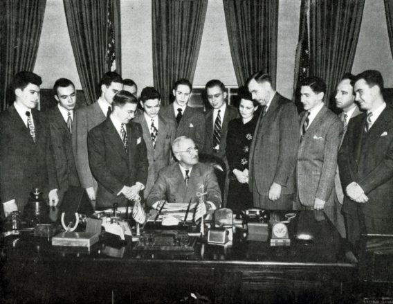A class of students stands behind Harry Truman in the Oval Office