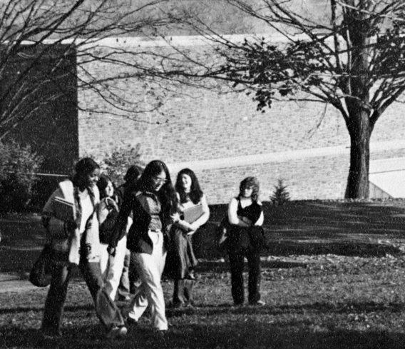 Female students walk across campus in front of a stone academic building